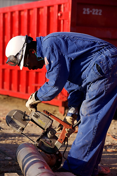 Stock photo of a man cutting pipe outdoors at a chemical plant