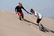 Gerson Valle, left, a sandboarding instructor at the oasis village of Huacachina in Peru, gives a hand to Tasha Clarbour of the United Kingdom, during her lesson.