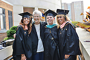 Three sisters who all graduated with their master's degrees pose with their grandmother following commencement ceremonies.