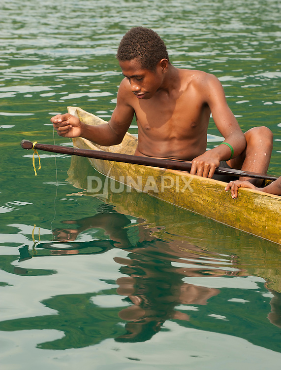 A boy fishes traditionally in front of Lobo Village, Triton Bay, Papua.