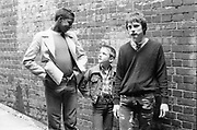 Felix, Neville and Ian stood in front of a brick wall, 1980s.