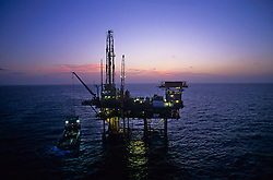 Stock photo of a jack up in the ocean at dusk