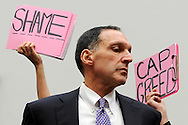 Protestors hold signs behind Richard Fuld, Chairman and CEO of Lehman Brothers Holdings, as he takes his seat to testify at a House Oversight and Government Reform Committee hearing on the causes and effects of the Lehman Brothers bankruptcy, during the 2008 financial crisis.