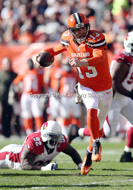 Cleveland Browns quarterback Josh McCown (13) is chased out of the pocket by Arizona Cardinals defensive end Frostee Rucker (92) as he runs for a gain of 10 yards in the second quarter during the 2015 week 8 regular season NFL football game against the Arizona Cardinals on Sunday, Nov. 1, 2015 in Cleveland. The Cardinals won the game 34-20. (©Paul Anthony Spinelli)
