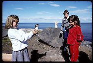 Eva Valsdottir, 9, shows feisty puffin chick to friend before releasing it to sea on Heimaey. Iceland
