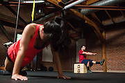 Victoria Hon completes pushups as Ben Babaei performs one-legged squats during an Introduction to CrossFit program at ThirdSpace Fitness in San Jose, California, on July 6, 2015. (Stan Olszewski/SOSKIphoto for Content Magazine)