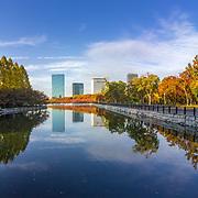 Cloudscape and skyline urban cityscape reflection at Osaka Castle Park, Japan.