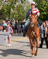 Moxie Redman being ridden by Julie Lawrence was all smiles as they marched down North Main Street for the annual July 4th parade Monday afternoon.  (Karen Bobotas/for the Laconia Daily Sun)
