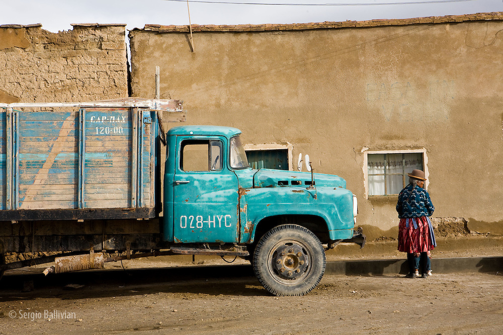 An old Aymara Indian lady waits for sunshine on the muddy streets of the city of Uyuni in Potosi, Bolivia.