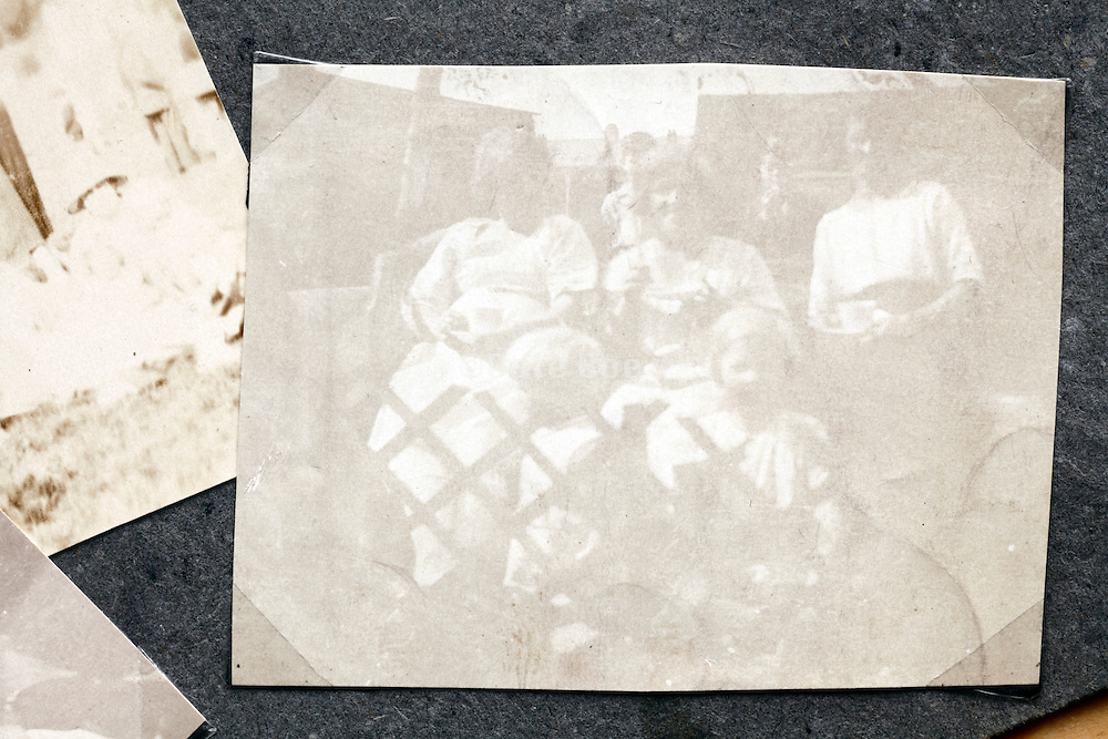 very faded image of women and children sitting in a garden 1920s