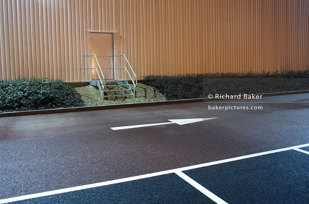 In front of an industrial doorway with a safety handrail and near empty parking bay markings, a stencilled arrow points from left to right at the DIRFT warehouse logistics park in Daventry, Northamptonshire England. Bright light glows from the warehouse wall, shining on to the car park creating an almost daylight landscape. This 365 acre site off Junction 18 of the M1 motorway is a hub for road, rail and service infrastructure, some 2.3m sq.ft. of distribution and manufacturing floorspace had been constructed by 2004 and occupiers including Tesco?s, Tibbett & Britten plc, Ingram Micro, Royal Mail, the W.H. Malcolm Group, Eddie Stobart Ltd, Wincanton and Exel, have been attracted to this logistics location.