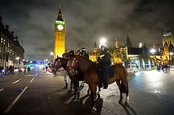© Licensed to London News Pictures. 05/11/2015. London, UK. Mounted police on horses guard the Houses of Parliament during An anti-capitalist  protest organised by the group Anonymous outside Parliament in Westminster on bonfire night 05, November 2015. Bonfire night, also known as Guy Fawkes night, is an annual commemoration of when Guy Fawkes, a member of the Gunpowder Plot, was arrested for attempting to blow up the House of Lords at parliament.   Photo credit: Ben Cawthra/LNP