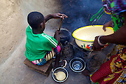 Balila helping her mother cook at their home in Tinguri, Ghana.