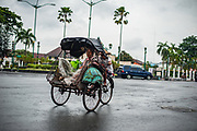 A young boy rides his mother in a becak on the Medan Merdeka (freedom square). During the period of Dutch rule this square was known as Koningsplein.