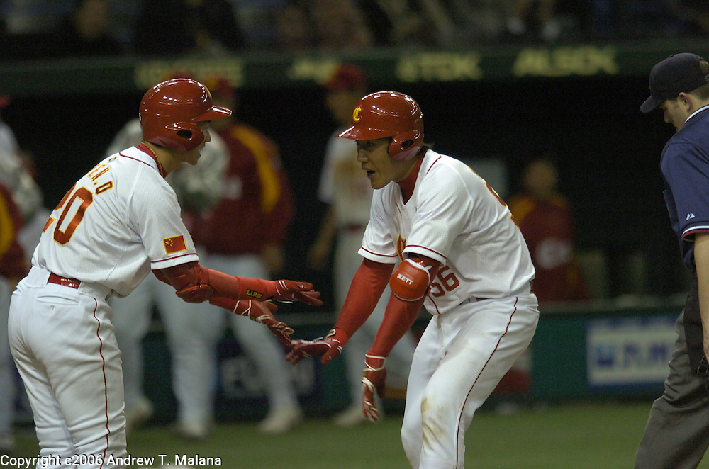 Team China catcher Wei Wang #56 is congratulated by#20 Qi Chen after Wang hit a two-run home in the 4th inning off of Team Japan's Koji Uehara. This is the first home run of the World Baseball Classic at Tokyo Dome, Tokyo, Japan..