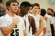 Rice's Ben Shungu (11) and the rest of the team listens to the National Anthem during the boys basketball game between the Essex Hornets and the Rice Green Knights at Rice Memorial high school on Tuesday night December 22, 2015 in South Burlington.(BRIAN JENKINS/for the FREE PRESS)