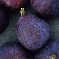 Close up of purple figs or Ficus carica Black Bursa with their white bloom sitting on tarnished metal plate