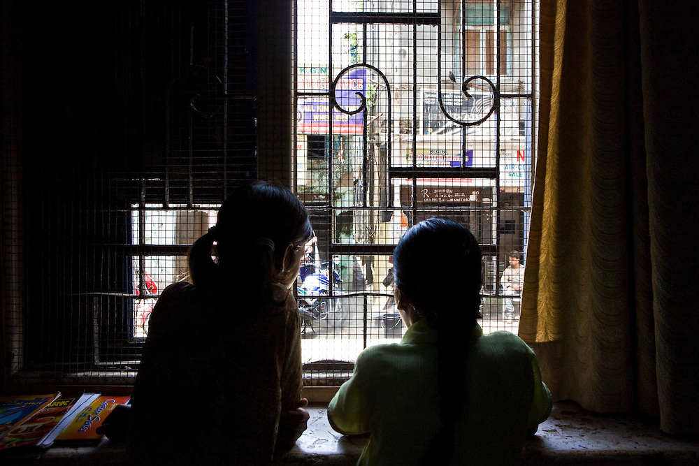 Two girls look out into the street from the Kamatipura Centre, Mumbai. The centre welcomes about 100 children every day from the surrounding red-light district. The centre is run by the Prerana organisation who specialise in children of the red-light districts in Mumbai.