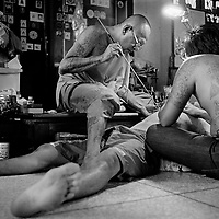 Nakhon Chai Si district, February 2010, Wat Bang Phra Temple. Thai people doing tattoo on the stomach of a Thai pious Bouddhist, in Nakhon Chai Si district, Thailand, about 50 km west of Bangkok. The temple is famous for its monks and their practice of giving Sak Yant tattoos with wooden bamboo and metal needless. Many believe that protective energy flows through the tattoos, keeping them safe from harm. It is not simply about getting a talisman tattoo here. The owner must activate it in order for it to serve as a lifesaving conduit. He or she must respect the precepts set by the head master.
