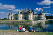 Tourists at the Chateau Chambord in the Loire Valley, France (Val de la Loire).  Impressive turrets and towers are reflected in the waters of the moat which was originally to repel invaders from the castle.
