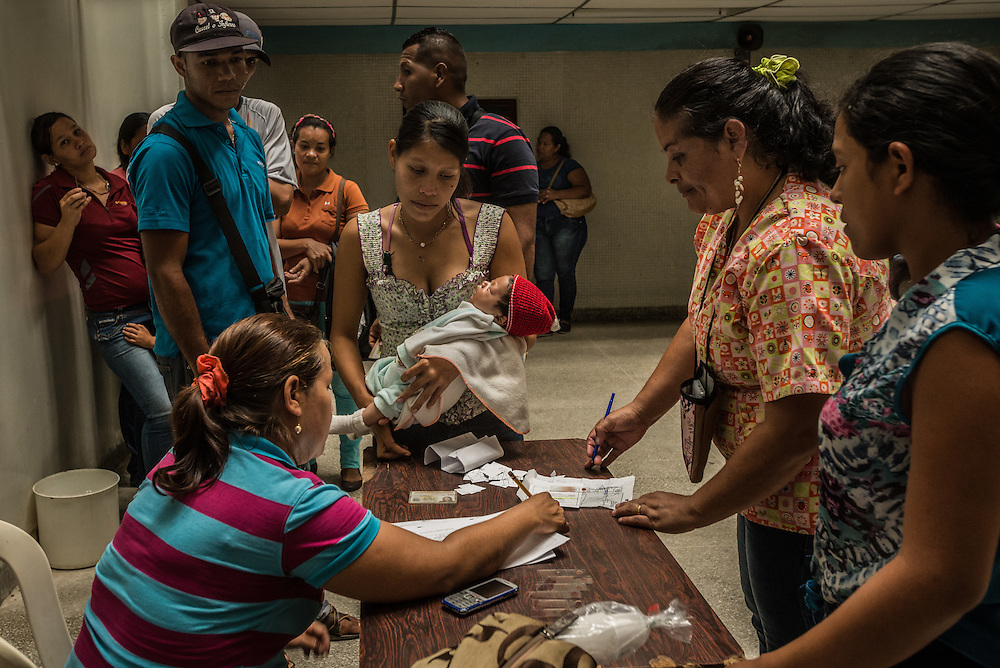 """SAN FELIX, VENEZUELA - MAY 24, 2016: Hundreds of people overflow a small clinic, all with symptoms of malaria: fevers, icy chills and uncontrollable tremors. A handful of doctors and hospital staff tried their best to test each patient for malaria: pricking their ears for a blood sample in a room without air conditioning and no lights because the government had cut power to save electricity. There were no medicines to be distributed, because the health ministry had not delivered any this day. Frustrated patients protested in the street outside of the hospital pleading for malaria medicine to be delivered.  Dr. Griselda Bello waved her hands helplessly to tell yet another patient that there was no medicine that day. """"Come back tomorrow at 10 a.m.,"""" she said. """"My God,"""" the patient said. """"Someone might die by then."""" """"Indeed they might,"""" she said. The spread of malaria in Venezuela is a state secret. Since 2007, the government has not submitted annual epidemiological reports on the disease and says there is no epidemic. But the most recent report, obtained by The New York Times from Venezuelan doctors involved in compiling it, confirms a surge is underway.  Last year, malaria cases rose 56% to 136,000 cases, the highest level in 75 years when the state began efforts to eradicate the disease, according to the report. Malaria has cut a wide swath through the country with cases now present in half of its 23 states. And among the strains present here is Plasmodim falciparum, the most fatal and severe form of the disease.   PHOTO: Meridith Kohut for The New York Times"""