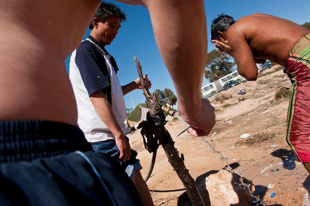 Des réfugiés font leur toilette au camp humanitaire Choucha à 8km de la frontière Libyenne. Plus de 140 000 réfugiés ont déjà quitté la Libye par la Tunisie ou l'Egypte et des milliers continuent d'arriver chaque jours. Mercredi 2 Mars 2011, camp humanitaire Choucha, Tunisie..© Benjamin Girette / AP