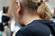 close up of a male person wearing his hair in a ponytail