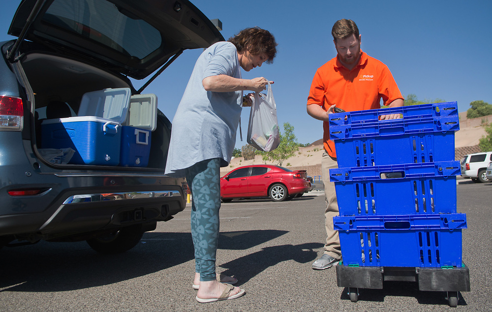 mkb063017b/living/Marla Brose --  Patricia Di Vasto checks inside one of her bags of groceries as Walmart's Logan Huntington, an online grocery associate, loads Di Vasto's online ordered groceries into her car, Friday, June 30, 2017, in Rio Rancho, N.M. (Marla Brose/Albuquerque Journal)