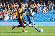 Brighton midfielder, winger, Kazenga LuaLua takes the ball away from \Hull City midfielder Moses Odubajo during the Sky Bet Championship match between Brighton and Hove Albion and Hull City at the American Express Community Stadium, Brighton and Hove, England on 12 September 2015. Photo by Phil Duncan.