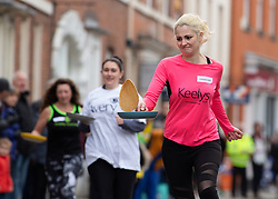 © Licensed to London News Pictures. 05/03/2019. Lichfield, Staffordshire, UK. The annual Shrove Tuesday pancake race taking place in Bore Street in the City Centre of Lichfield. Pictured, Lorraine Dewar, right, in a ladies race heat. The event features races for men, women, children and those in fancy dress. The runners are supported by the voice of Town Crier Ken Knowles and the overall winner walks away with a brass and wooden Shrove Tuesday trophy. Photo credit: Dave Warren/LNP