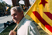 Supporters of Catalan independence wave Catalan flags through the Arc de Triomf (Triumphal Arch) in Barcelona on October 10, 2017. Spain's worst political crisis in a generation will come to a head as Catalonia's leader could declare independence from Madrid in a move likely to send shockwaves through Europe.  10, 2017 in Barcelona, Spain. Christian Mantuano / OneShot
