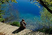 Woman sitting by lake, Plitvice National Park, Croatia