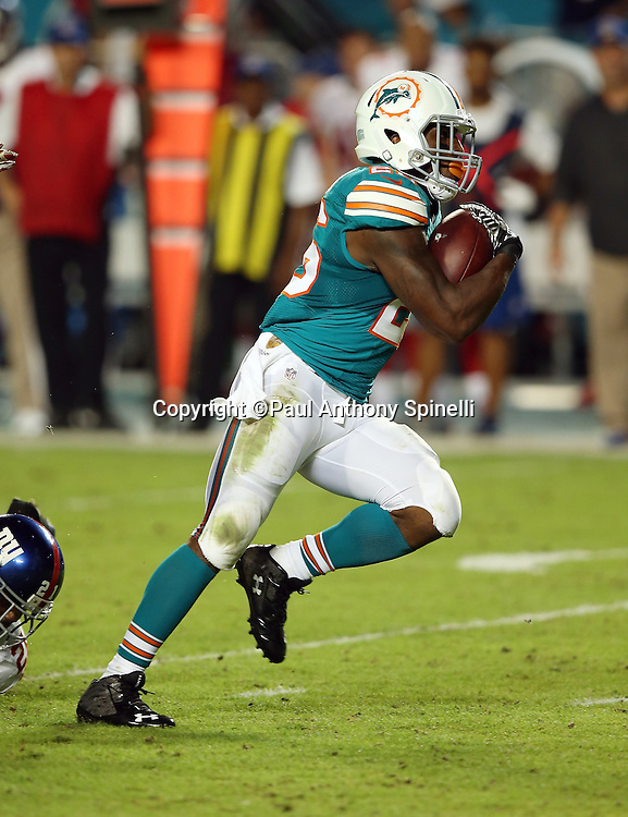 Miami Dolphins running back Lamar Miller (26) runs for a 26 yard second quarter touchdown good for a 14-10 Dolphins lead during the NFL week 14 regular season football game against the New York Giants on Monday, Dec. 14, 2015 in Miami Gardens, Fla. The Giants won the game 31-24. (©Paul Anthony Spinelli)