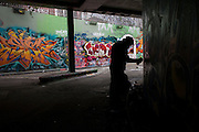 Sinister graffiti artist silhouette sprays walls in underpass tunnel in Waterloo.