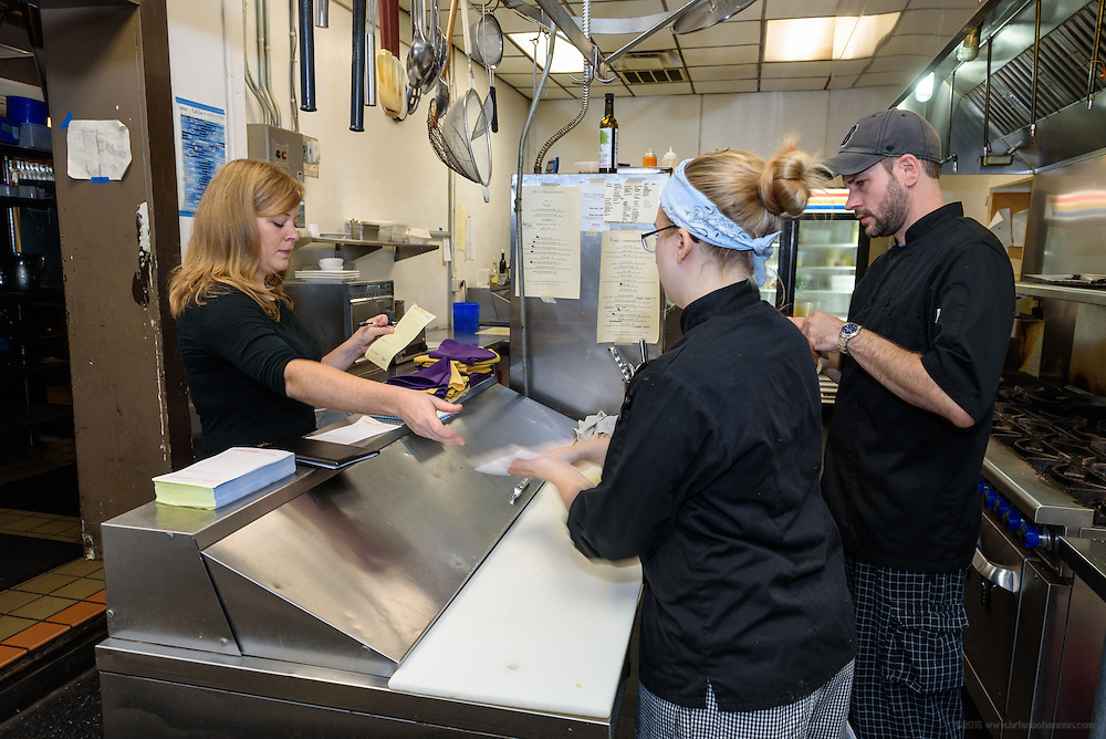 Server Rosalie Guthrie passes a lunch order to Chef Victoria Jump as Chef de Cuisine Allen Grimm looks on. Lunchtime in the kitchen at Lilly's Monday, Aug. 15, 2016 with Chef/Owner Kathy Cary and staff. (Photo by Brian Bohannon)