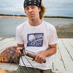 Commercial clammer Will Hamill holds a clam rake at Pine Point in Scarborough, Maine.