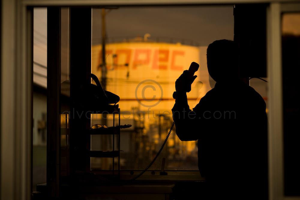silueta funcionario dentro de garita  en planta maipú. sin dolor. Copec, 80 años. Santiago de Chile. {date} (©Alvaro de la Fuente/Triple.cl)