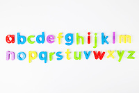 Alphabet magnets arranged in order over white background