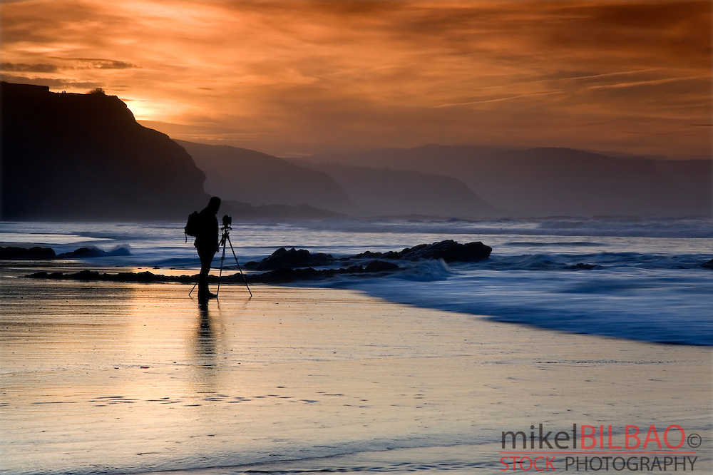 Photographer at sunset on a beach.<br /> Atxabiribil beach. Sopelana, Biscay, Basque Country, Spain, Europe.