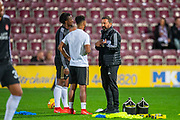 Aberdeen manager Derek McInnes (right) speaks with Greg Leigh (#3) of Aberdeen FC and Shay Logan (#2) of Aberdeen FC (white t-shirt) during the warm up before the Betfred Scottish Football League Cup quarter final match between Heart of Midlothian FC and Aberdeen FC at Tynecastle Stadium, Edinburgh, Scotland on 25 September 2019.