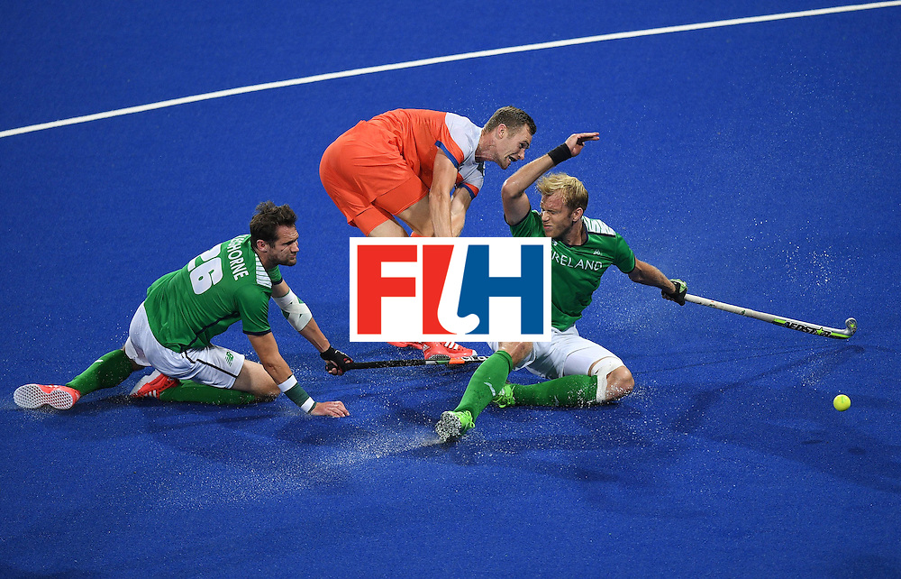 Netherland's Mirco Pruijser hits past Ireland's Paul Gleghorne (L) and Conor Harte during the men's field hockey Netherlands vs Ireland match of the Rio 2016 Olympics Games at the Olympic Hockey Centre in Rio de Janeiro on August, 7 2016. / AFP / MANAN VATSYAYANA        (Photo credit should read MANAN VATSYAYANA/AFP/Getty Images)