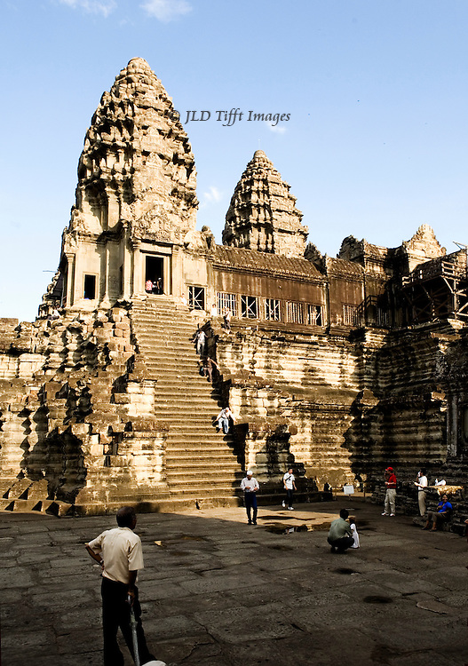 Angkor Wat: third or upper level with steep stairs up to the central tower and tourists struggling to climb them.