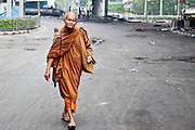18 MAY 2010 - BANGKOK, THAILAND:   A Buddhist monk walks through Din Daeng intersection in Bangkok Tuesday. The intersection has been under periodic sniper fire from unidentified snipers near Thai military lines. Violent unrest continued in Bangkok again Tuesday nearly a week after Thai troops started firing on protesters and Bangkok residents took to the streets in violent protest against the government. Tuesday was not as violent as previous days however. Although protesters continued to set up roadblocks and flaming tire barricades across parts of the city, there was not as much gunfire from the government lines. The most active protesters were at the Din Daeng Intersection about a mile from the Red Shirts' Ratchaprasong camp.  PHOTO BY JACK KURTZ