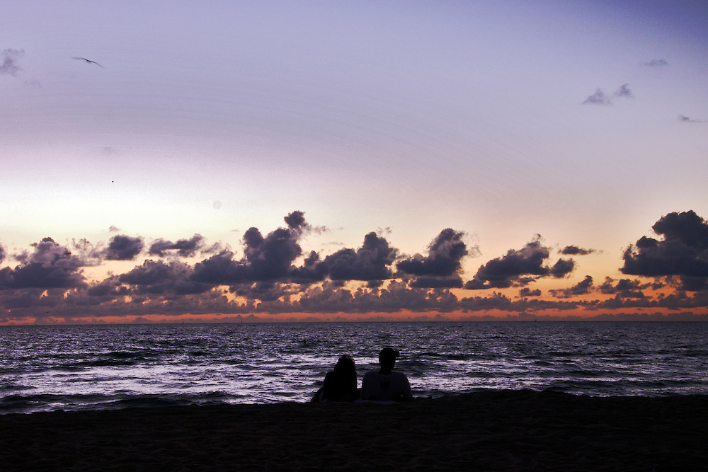 Couple relaxing at the beach at dawn, in Miami Beach