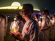 "11 FEBRUARY 2016 - KHLONG LUANG, PATHUM THANI, THAILAND:  People participate in the procession around the pagoda during the Makha Bucha Day service at Wat Phra Dhammakaya.  Makha Bucha Day is a public holiday in Cambodia, Laos, Myanmar and Thailand. Many people go to the temple to perform merit-making activities on Makha Bucha Day, which marks four important events in Buddhism: 1,250 disciples came to see the Buddha without being summoned, all of them were Arhantas, or Enlightened Ones, and all were ordained by the Buddha himself. The Buddha gave those Arhantas the principles of Buddhism. In Thailand, this teaching has been dubbed the ""Heart of Buddhism."" Wat Phra Dhammakaya is the center of the Dhammakaya Movement, a Buddhist sect founded in the 1970s and led by Phra Dhammachayo. Makha Bucha Day is one of the most important holy days on the Thai Buddhist calender.     PHOTO BY JACK KURTZ"