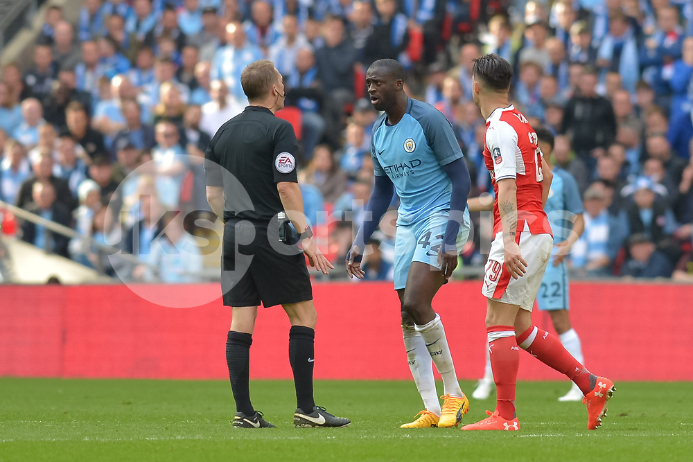 Yaya Touré of Manchester City speaks with referee Craig Pawson during the The FA Cup Semi Final match between Arsenal and Manchester City at Wembley Stadium, London, England on 23 April 2017. Photo by Vince Mignott.