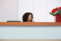 Receptionist sitting behind reception desk talking on Telephone