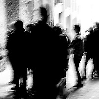 A crowd of people, blurred, standing in an alley in Seattle Washington.