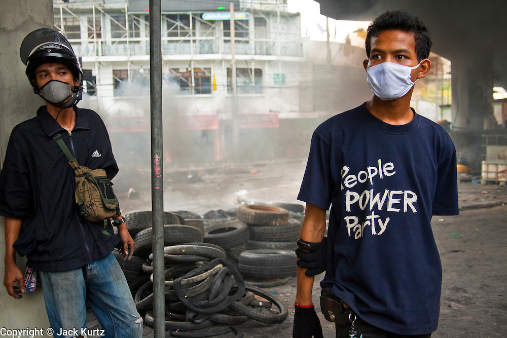 18 MAY 2010 - BANGKOK, THAILAND: An anti government protester with a People Power Party tee shirt at a tire barricade at Din Daeng Intersection in Bangkok Tuesday. The PPP is the now banned political party of ousted and exiled former Prime Minister Thaksin Shinawatra. The intersection has been under periodic sniper fire from unidentified snipers near Thai military lines. Violent unrest continued in Bangkok again Tuesday nearly a week after Thai troops started firing on protesters and Bangkok residents took to the streets in violent protest against the government. Tuesday was not as violent as previous days however. Although protesters continued to set up roadblocks and flaming tire barricades across parts of the city, there was not as much gunfire from the government lines. The most active protesters were at the Din Daeng Intersection about a mile from the Red Shirts' Ratchaprasong camp.  PHOTO BY JACK KURTZ