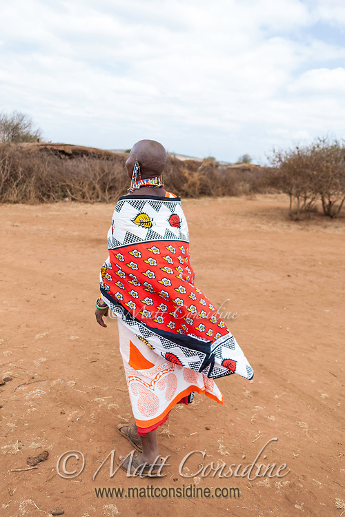 Tall elegant African Masai woman in colorful traditional clothing and beadwork walking away across dry brown earth in Kenya, Africa (photo by Wildlife Photographer Matt Considine)
